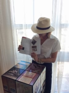 "Maribel Alvarez reading through ""Cutting Edge Art in Havana"" while preparing for her next trip hosted by Havana VIP Tours and ARTempoCuba. Photographed with work by featured mixed media artist, Kadir Lopez."